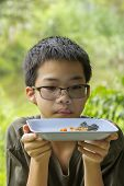 image of plate fish food  - Portrait of Asian Thai pensive boy looks at fish bone of white perch fish fried eaten clearly on plate - JPG