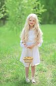 stock photo of natural blonde  - Spring portrait of cute little girl in white dress with long blonde hair holding a basket of yellow dandelions on a nature  - JPG