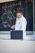pic of senior class  - Senior chemistry professor writing on the board while having a chalk and blackboard lecture  - JPG