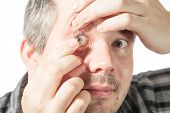 image of contact lenses  - Picture of a man putting on a contact lens - JPG