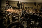 picture of rockabilly  - Mechanic doing lathe works in motorcycle customs garage  - JPG