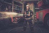 foto of firefighter  - Firefighter holding water hose near truck with equipment  - JPG