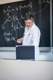 image of professor  - Senior chemistry professor writing on the board while having a chalk and blackboard lecture  - JPG