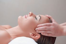 image of therapist  - Facial massage. Top view of attractive young woman lying on back and keeping her eyes closed while massage therapist massaging her face ** Note: Shallow depth of field - JPG