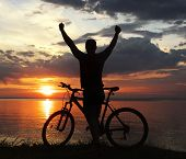 stock photo of dirt-bike  - silhouette of a man with a mountain bike on the river bank at sunset - JPG