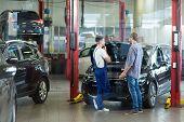 stock photo of car repair shop  - Man having problems with car visiting repair shop - JPG