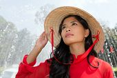 stock photo of conic  - Vietnamese woman in a traditional red outfit and conical hat standing in front of a fountain - JPG