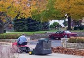 picture of leaf-blower  - man clearing leaves in street and parking lot - JPG