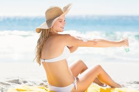 picture of sun tan lotion  - Pretty blonde woman spreading sun tan lotion on her arms at the beach - JPG