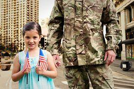 stock photo of reunited  - Soldier reunited with his daughter against new york street - JPG