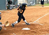 foto of fastpitch  - Fastpitch softball girl after having made contact with softball in mid swing - JPG
