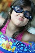 foto of floaties  - Little girl in pink swimsuit with goggles and floatie ready to jump in the pool making a funny face with pursed lips. ** Note: Shallow depth of field - JPG