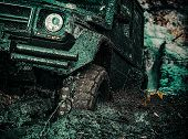 4x4 Travel Trekking. Offroad Vehicle Coming Out Of A Mud Hole Hazard. Bottom View To Big Offroad Car poster