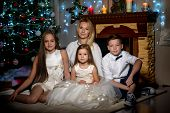 Happy Young Family With Children At Christmas Near A Christmas Tree And A Fireplace. The Concept Of  poster