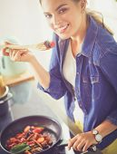 Young woman cooking healthy food holding a pan with vegetables is it. Healthy lifestyle, cooking at  poster