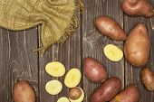 Lot Of Whole Lot Of Slices Of Fresh Red Potato Francelina Variety On Jute Cloth Flatlay On Brown Woo poster