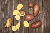 Group Of Three Whole Lot Of Slices Of Fresh Red Potato Francelina Variety Flatlay On Brown Wood poster