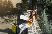 Happy Laughing Traveler Tourist Woman In Yellow Clothes Hat With Suitcase City Map Sitting On Stone  poster