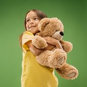 Happy Teen Girl Standing, Smiling With Toy Bear Isolated On Trendy Studio Background. Beautiful Fema poster