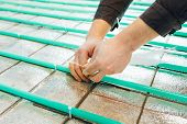 underfloor heating installation, pipes fastening with tie wraps by hands poster