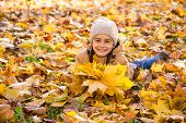 Autumn Portrait: Cute Smiling Little Girl Lying On The Fallen Leaves And Holding The Bouquet Of Yell poster