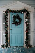 Winter Wreath Hanging On A Door Of House Decorated By Christmas Pine Branch With Red Baubles And Dec poster