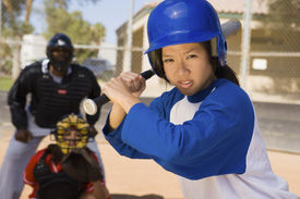 foto of umpire  - Young Asian softball player holding bat with keeper and umpire in the background - JPG