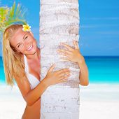 Sexy blond woman with frangipani flower in head hug palm tree on beautiful seascape background, luxu