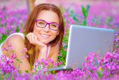Closeup portrait of cheerful student girl lying down on purple floral field with laptop, wearing gla