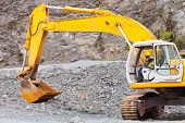 stock photo of heavy equipment operator  - african road construction worker operating excavator on construction site - JPG