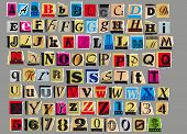 image of glyphs  - Letters and numbers cut out from old magazines and newspapers Isolated on gray background - JPG