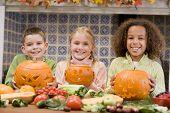 Постер, плакат: Три молодых друзей на Хэллоуин с Jack O фонарями и продовольствия улыбается