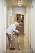 Full length of a tired elderly woman with walker standing in hospital passageway
