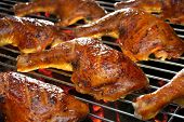 picture of charcoal  - Grilled chicken thigh on the flaming grill - JPG