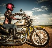 MOSCOW, RUSSIA-JULY 7, 2013: Biker girl on Legendary bike Harley Sportster. Harley-Davidson sustains