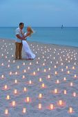 image of propose  - A man propose marriage to woman at sea beach in many candle lights against sunset- St.Valentines Day romantic concept