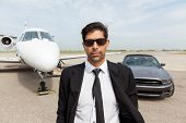 Portrait of confident male entrepreneur in front of car and private jet