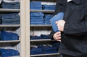 foto of shoplifting  - jeans being stolen by a shoplifter in a shop - JPG