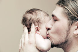 stock photo of cuddle  - Father with his young baby cuddling and kissing him on cheek - JPG