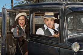 picture of tommy-gun  - 1920s female gangster firing machine gun from car with partner - JPG
