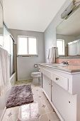 pic of linoleum  - White bathroom with old vanity cabinet linoleum and soft rug - JPG