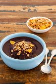 picture of brazilian food  - Brazilian dessert Acai in blue bowl with muesli and spoon on wooden table close - JPG