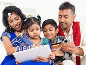 stock photo of ebusiness  - Indian Asian family using digital tablet pc computer online shopping with credit card at home - JPG