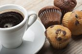 foto of chocolate muffin  - muffin with chocolate chips and cup of coffee on wooden table