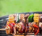 stock photo of barbie  - Delicious grilled meat skewers on fire - JPG