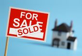 foto of yard sale  - Real estate agent for sale sign with sold sticker and house in background - JPG
