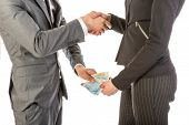 stock photo of bribery  - Man gives woman money while shaking hands over a white background - JPG