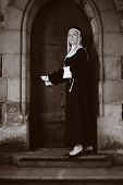 stock photo of covenant  - Nice girl posing like a nun walking by church in Prague for religion style photos.