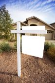 picture of inference  - A home for sale has a for sale sign that is blank for copy space - JPG