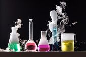 pic of shoot out  - Glass in a chemical laboratory filled with colored liquid during the reaction  - JPG